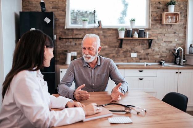 Homem sênior que fala a um doutor fêmea em uma visita home.