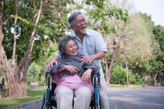 Homem sênior que importa-se com a esposa deficiente em sua cadeira de rodas.