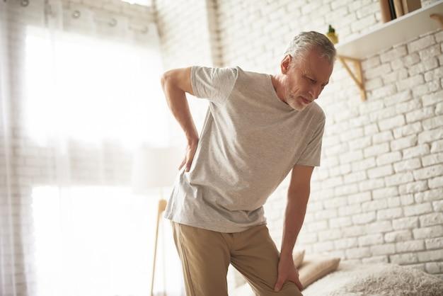 Homem sênior que sofre a dor lombar da fadiga da parte traseira da parte traseira.