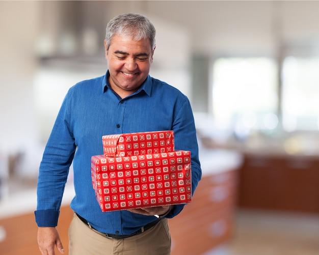 Homem sênior que sorri olhando para os presentes que ele realiza em sua mão