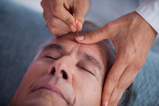 Homem sênior, recebendo massagem na cabeça do fisioterapeuta