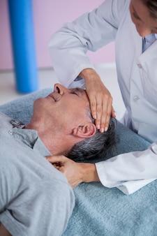 Homem sênior, recebendo, pescoço, massagem, de, fisioterapeuta