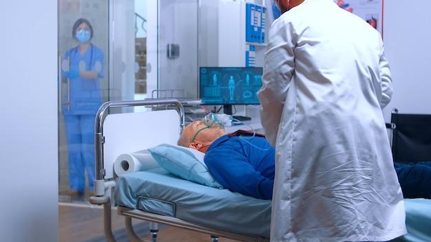 Homem sênior recebendo uma máscara de oxigênio do médico para ajudá-lo a respirar melhor durante a crise de saúde do coronavírus covid-19. clínica particular de medicina médica ou tratamento hospitalar
