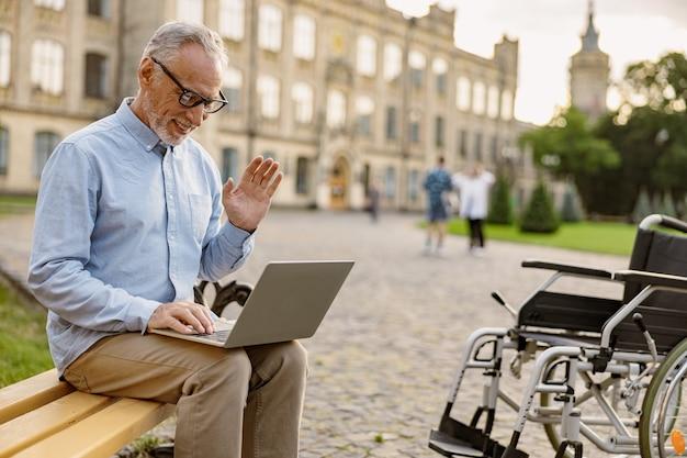 Homem sênior, recuperando paciente com cadeira de rodas, fazendo videochamada, trabalhando em um laptop enquanto está sentado