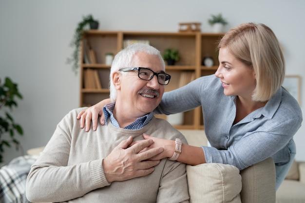 Homem sênior repousante no sofá, olhando para sua filha loira, parada por perto, sorrindo para o pai e abraçando-o