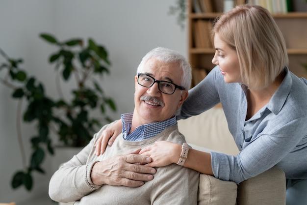 Homem sênior repousante no sofá, segurando a mão de sua filha loira, parada por perto e abraçando o pai