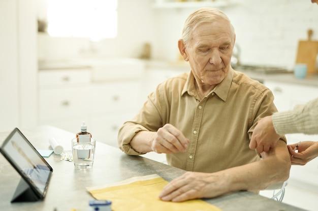 Homem sênior reservado se preparando para verificação de pressão arterial
