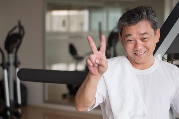 Homem sênior saudável e feliz malhando na academia, dando o primeiro gesto com o dedo, conceito de vitória ou sucesso