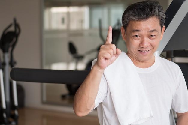 Homem sênior saudável e feliz malhando na academia, dando o primeiro gesto com o dedo, ganhando ou conceito de sucesso