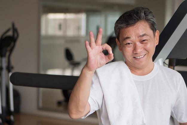 Homem sênior saudável e feliz malhando na academia, fazendo gestos de ok com o dedo, bom, vencendo, sucesso, conceito de aprovação