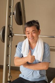 Homem sênior saudável e feliz malhando na academia, gesto de polegar para cima