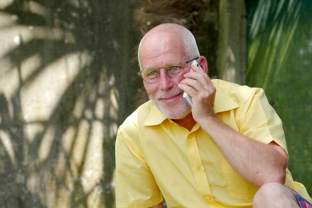 Homem sênior saudável no jardim ao ar livre do telefone