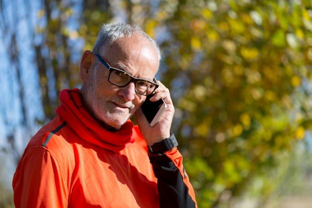Homem sênior saudável no parque ao ar livre do telefone