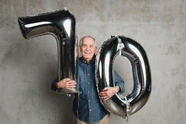 Homem sênior segurando balões de prata para comemorar os 70 anos