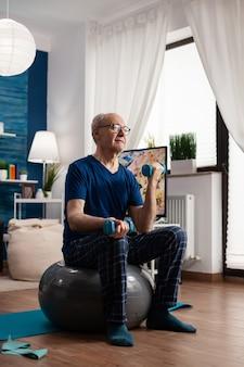 Homem sênior segurando halteres e fazendo exercícios com os braços, alongando os músculos do corpo