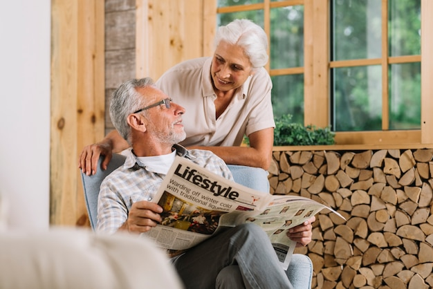 Homem sênior, segurando jornal, em, mão, olhar, esposa