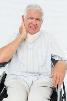 Homem sênior sentado em cadeira de rodas com colar cervical