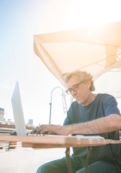 Homem sênior, sentando, em, ao ar livre, caf�, digitando, ligado, laptop