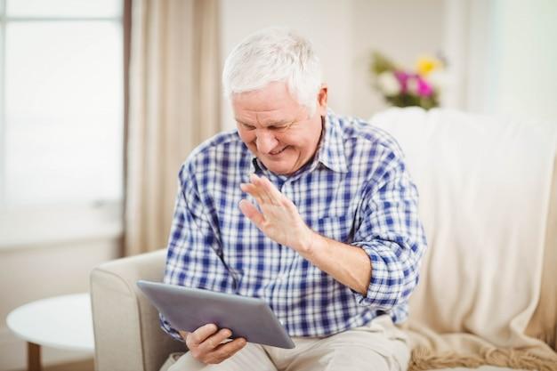 Homem sênior, sentar sofá, e, usando, tablete digital, em, sala de estar
