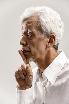 Homem sênior sério e assustado mantém o dedo da frente nos lábios, tenta manter a conspiração, diz: shh, faça silêncio, por favor. foto isolada de homem mostrando gesto de silêncio