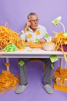 Homem sênior sério e criativo posa na mesa do escritório pensa em ideias criativas para o desenvolvimento design do site pondera sobre algo cercado por pastas prepara o projeto usa roupas formais