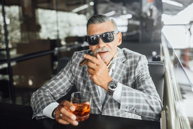 Homem sênior sério sentado na varanda, fumando um cigarro