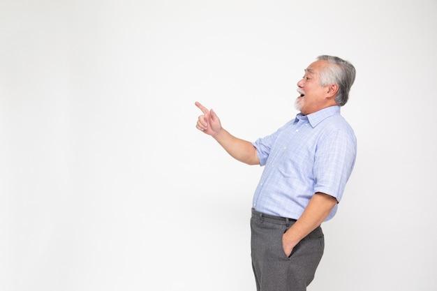 Homem senior sorridente apontando para algo,