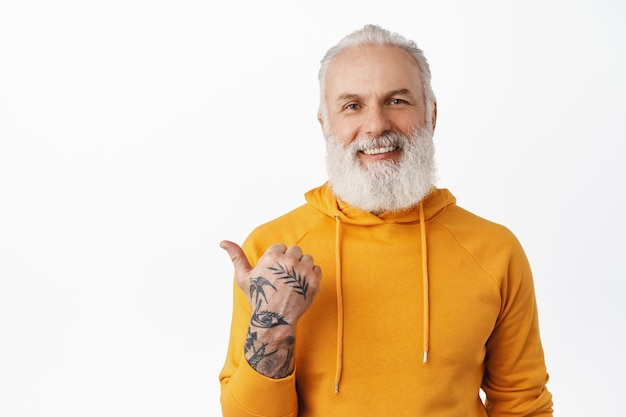 Homem sênior sorridente com tatuagens apontando para a esquerda e parecendo feliz, dê conselhos, visite esta página, clique no gesto de link, em pé com um moletom laranja contra a parede branca