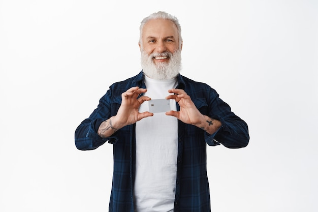 Homem sênior sorridente com tatuagens mostrando cartão de crédito, recomendando seu banco, satisfeito com o serviço, em pé sobre uma parede branca