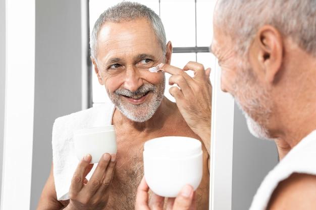 Homem sênior sorridente de close-up passando creme