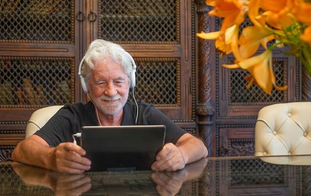 Homem sênior sorridente usando dispositivo eletrônico com fones de ouvido. sentado em uma mesa de madeira