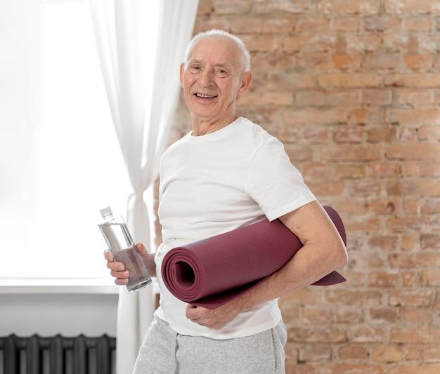 Homem sênior, tiro médio, segurando um tapete de ioga