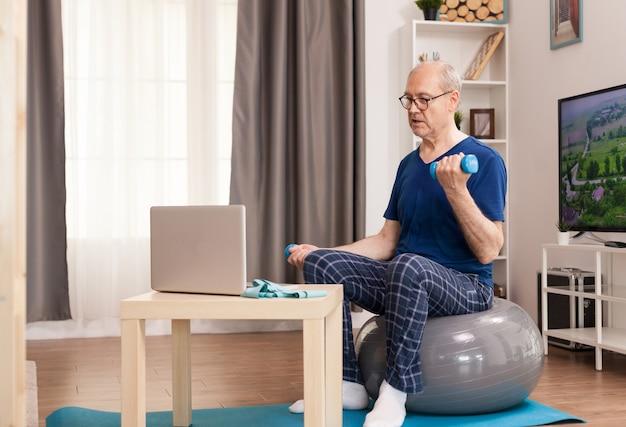 Homem sênior treinando com o treinador online sentado na bola suíça no meio da sala
