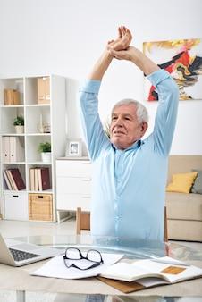 Homem sênior um pouco cansado, levantando as mãos na cabeça enquanto se exercita na mesa em frente ao laptop durante o trabalho em casa