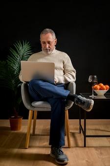 Homem sênior, usando computador portátil, perto, tabela