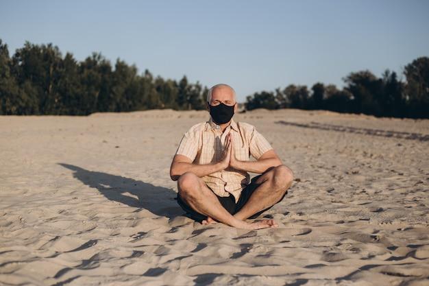 Homem sênior usando máscara protetora de medicina em pose de lótus, sentado na areia. conceito de calma e meditação.