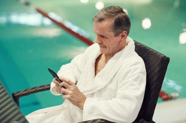 Homem sênior, usando, smartphone, em, spa resort