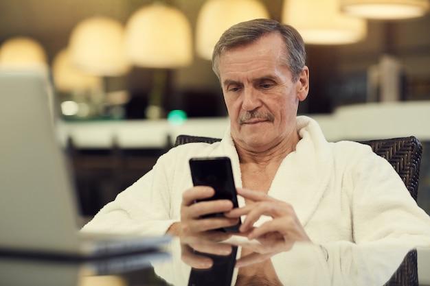 Homem sênior usando smartphone no spa