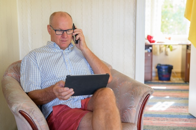 Homem sênior usando tablet digital e telefone em casa