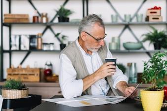 Homem sênior, xícara café, em, mão, jornal leitura
