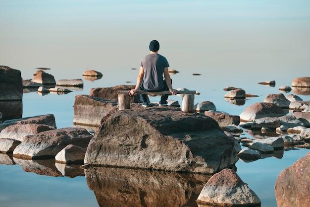 Homem senta-se em um banco de madeira e admira a calma completa do mar. vista traseira.