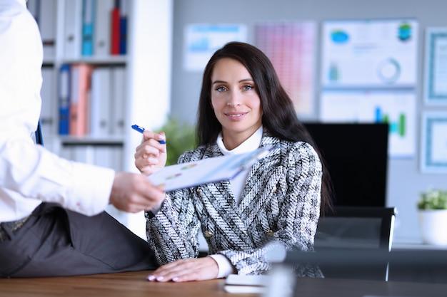 Homem senta-se em um escritório na mesa na frente da mulher