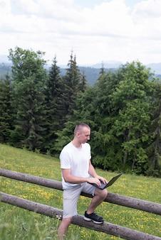 Homem senta-se em uma cerca de madeira e trabalha com um laptop perto do campo e floresta de coníferas.