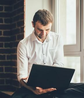 Homem senta-se no peitoril da janela e trabalha atrás do laptop no escritório