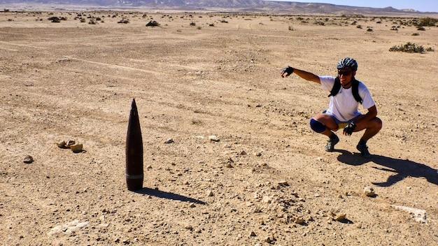 Homem senta-se perto de big shell no fundo do deserto de negev. israel.