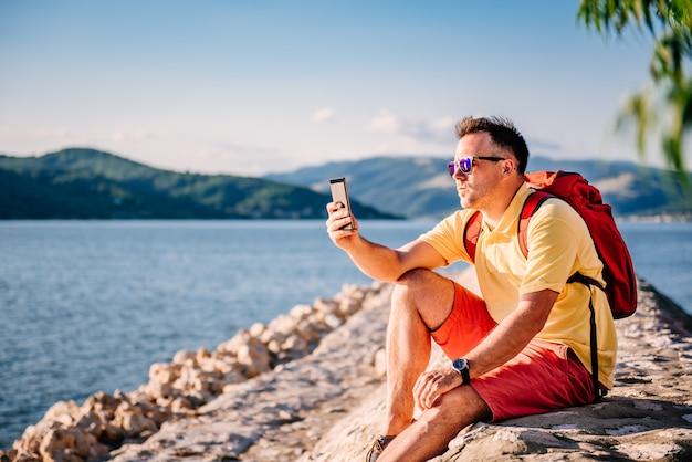 Homem sentado à beira-mar e tirar fotos com o telefone inteligente