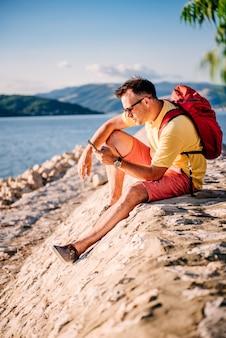 Homem sentado à beira-mar e usando telefone inteligente