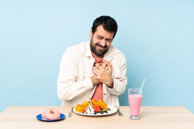 Homem sentado a uma mesa tomando waffles e um milk-shake no café da manhã com uma dor no coração