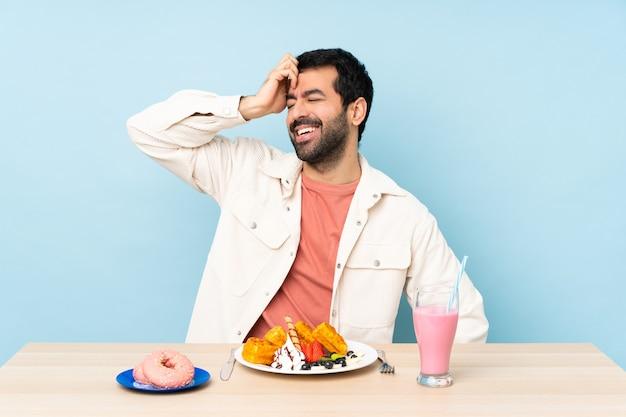 Homem sentado a uma mesa tomando waffles e um milkshake no café da manhã sorrindo muito