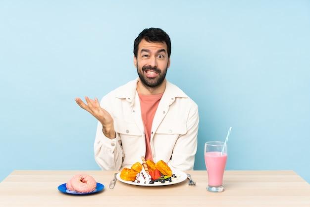 Homem sentado a uma mesa tomando waffles no café da manhã e um milkshake fazendo um gesto de dúvida